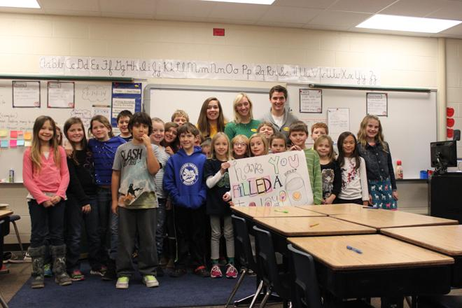 Seniors Katie Harding, Brooke Mattson and Chris Semrinec pose for a picture with Barb Andres's third-grade class after the presentation.