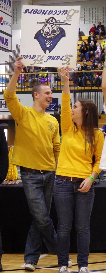 "Senior captains Karl Johnson and Kaia Hayes have some fun representing the team in the ""Parade of Schools"" during the opening ceremonies."