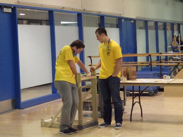 Junior Nick Johnson and senior Eric VanDyke prepare for the event Scrambler. The event required the duo to build a vehicle that traveled quickly but also would stop so an egg in the front of the vehicle would not break and hit the wall at the end of the runway (Michalski).